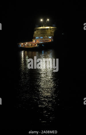Borneo, Indonesia - July 2019: Maersk owned oil field support vessel standing by on an oil field by night