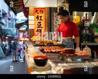 Young Woman preparing taiwanese / japanese wheel cakes (Imagawayaki) with red azuki bean filling  at street food shop in jiufen old street. - Stock Photo