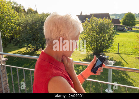 Senior woman trying to read a message in the sun on a cell phone - Stock Photo