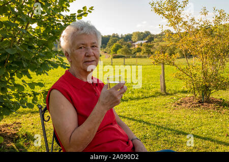 old lady sitting comfortably in the garden and drinking a glass of water - Stock Photo