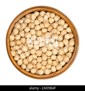 Dried chickpeas in wooden bowl. Light tan Kabuli chickpea variety. Chick peas, Cicer arietinum, high protein legume and ingredient of hummus. - Stock Photo
