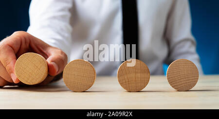 Businessman placing four blank wooden circles in a row on a desk. - Stock Photo