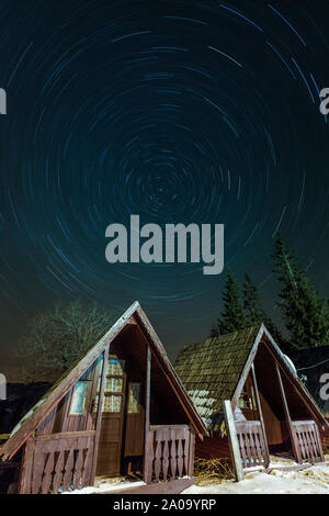 Star trails over small cabins, shot in Romania mountains - Stock Photo