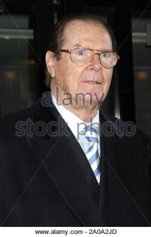 New York, NY - Sir Roger Moore, the actor best known for his role as the spy in seven of the James Bond films, is escorted into an office building in New York. The actor is currently promoting his book, 'Bond on Bond : Reflections on Fifty Years of James Bond Movies'. AKM-GSI November 12, 2012 - Stock Photo