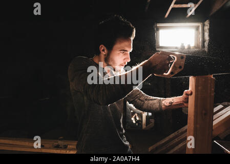 Young Man Saws Wood in Workshop - Stock Photo