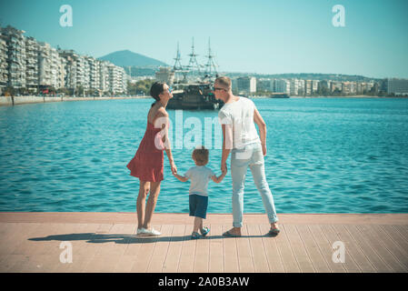 Mother and father going to kiss near their child. Happy family spend time together, holding hands, sea background. Parents with son stand on seafront, - Stock Photo