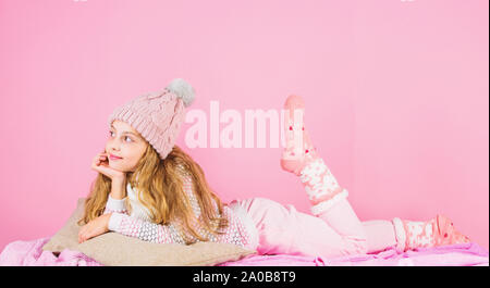 Kid girl wear cute knitted fashionable hat and scarf accessory. Winter fashion accessory. Winter accessory concept. Girl long hair dreamy mood pink background. Kid smiling wear knitted accessory. - Stock Photo