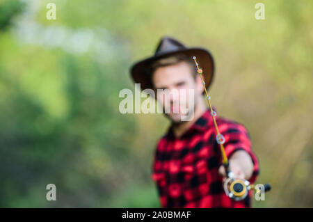 Hook and bait. Fishing hobby. Guy in cowboy hat fishing equipment nature background defocused. Hipster fisherman hold rod spinning selective focus. Hope for nice fishing. Fishing day. Proper fishhook. - Stock Photo