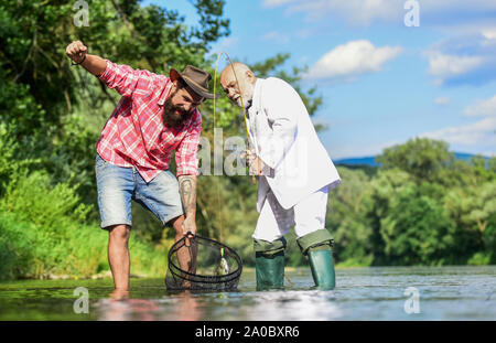 Freshwater fish. Bearded man and brutal hipster fishing. Oh happy day. Fishing team. Family day. Hobby and recreation. Catching fish with soulmate. Friends catching fish. Fish trapped in net. - Stock Photo