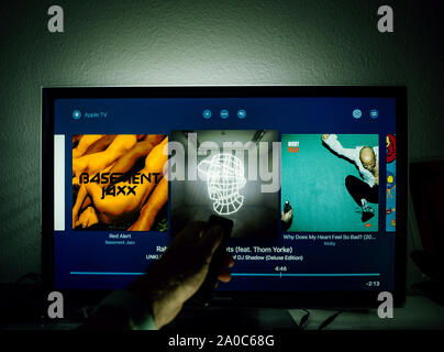 Paris, France - Circa 2019: Man surfing with remote Apple TV menu on Panasonic Plasma tv living room surf for Artist Playlists Electronic music - Stock Photo