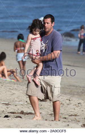 Malibu, CA - Adam Sandler plays in the water with daughter Sadie, while wife Jackie keeps youngest daughter Sunny in her arms. Little Sunny got plenty of love from mommy and daddy as they both took turns holding her on this Labor Day. Sadie played kissy with daddy in his arms as the sun set for the evening. GSI Media September 7, 2009 - Stock Photo