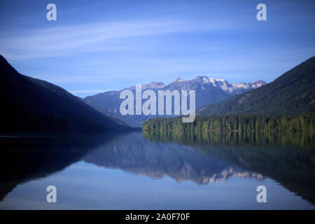 Snow capped mountains, green conifers and blue sky reflecting in Birkenhead lake as in a mirror, on the still water, in a secluded destination of BC - Stock Photo