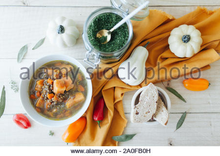 White bowl of pumpkin soup with cream pumpkins, orange and red sweet peppers, green parsley flakes, mustard napkin, brass spoon on wooden background. - Stock Photo