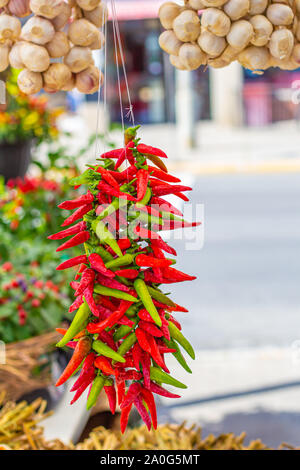 A bunch of small red and green chili peppers hangs on strings below some garlic in a farmer's market. - Stock Photo