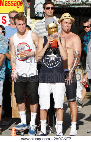 Venice Beach, CA - Justin Bieber went to Venice Beach this afternoon, looking for a day away from his normal schedule. To accomplish that, he decided to wear a gold mask over his face, blocking the world from recognizing him. Along with his dad and best friend, the three played a few hoops and walked up and down the boardwalk, watching the sidewalk performers do what they do best. They also decided to stop at one of the dozens of tattoo shops for some fresh ink. Justin got a tattoo of Jesus Christ on the back of his left calve muscle, while his father chose a tropical flower design running up - Stock Photo
