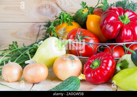 Natural homegrown food concept. Assorted fresh vegetables from new harvest collected in a wicker basket on wooden background. - Stock Photo
