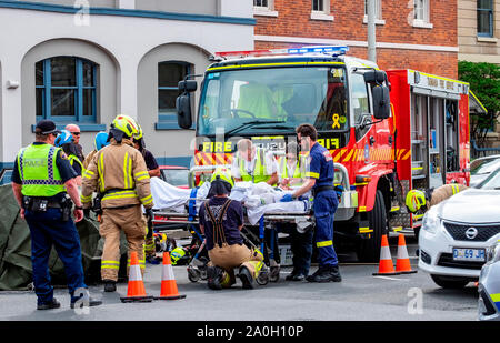 Firemen, police and paramedics rescue a woman trapped in her car in a traffic accident in the Hobart CBD Friday September 20 2019 - Stock Photo
