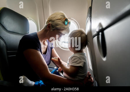 Mother with small baby son playing in the airplane during the flight