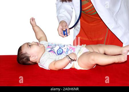 Pediatrician checking baby's heartbeat - Stock Photo