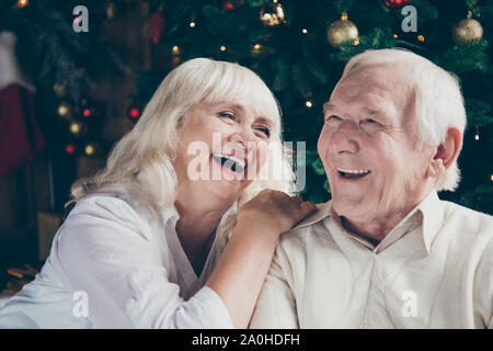 Close-up portrait of two nice cheerful delighted beautiful grey-haired married spouses husband and wife enjoying free time having fun joking near deco - Stock Photo