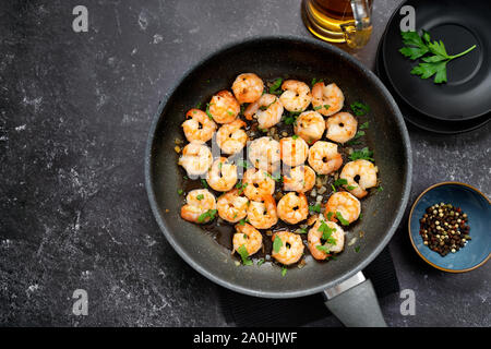 Top view of fried prawns in a pan on black background - Stock Photo