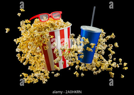 Paper striped bucket with popcorn, cup of drink and glasses isolated on black - Stock Photo