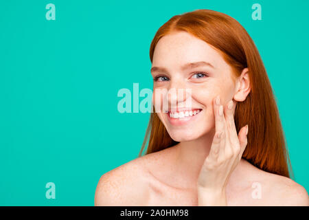 Advertising concept. Close-up portrait of nice cute gorgeous attractive cheerful red-haired girl with shiny pure clean skin, applying cream on cheek, - Stock Photo