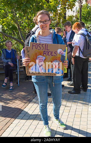 Bournemouth, Dorset UK. 20th September 2019. Protesters, young and old, gather in Bournemouth Square on a hot sunny day to protest against climate change and demand action against climate breakdown from government and businesses to do more. BCP (Bournemouth, Christchurch, Poole) Council have reportedly been threatened with legal action and could be taken to court until they produce proper timely climate change plans. Girl holding placard - Fossil fools. Credit: Carolyn Jenkins/Alamy Live News - Stock Photo