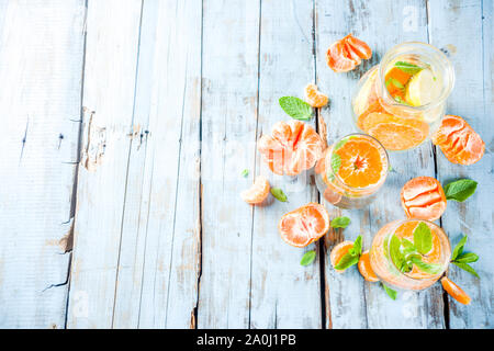 Summer tangerine citrus drink, lemonade or mojito, with fresh tangerines, lemons and mint on a blue wooden table, - Stock Photo