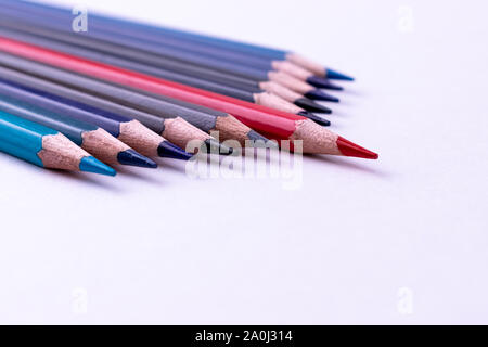 Red pencil standing out from others pencil on white background. Leadership, business success concept.