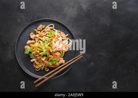 Udon stir-fry noodles with pork bowl and vegetables on black stone background. Asian cuisine. Top view. Copy space. - Stock Photo