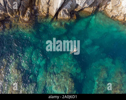 Birds eye view of a man swimming in a tropical lagoon. - Stock Photo