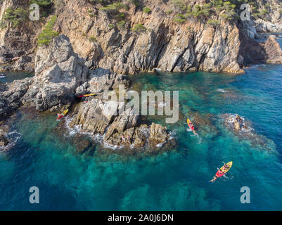 A group of friends playing and kayaking in a Mediterranean cove. - Stock Photo