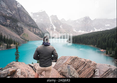 Man standing on rocky ledge overlooking Moraine Lake in the mountains. - Stock Photo