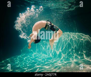 Underwater image of teenage boy doing a flip underwater. - Stock Photo