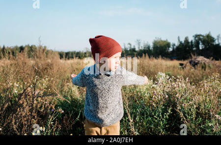 young boy playing, pretending to be an aeroplane outside at sunset - Stock Photo