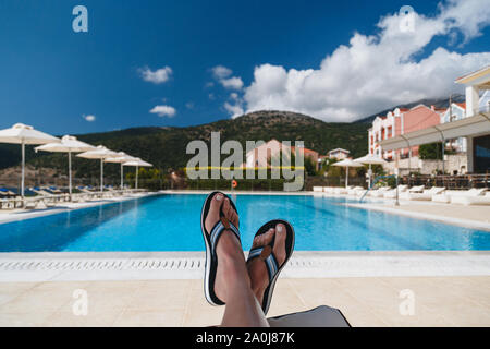 Close up view of young woman feet in blue flip-flops lying on a sun lounger with a swimming pool and blue sky at the background. Kefalonia island