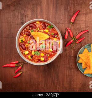 Chili con carne with chilli peppers and nachos, overhead square shot on a dark rustic wooden background - Stock Photo