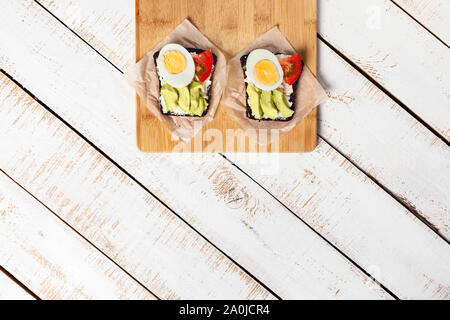 Two diet sandwiches with avocado, tomato, cream cheese on white wooden background. Food for vegetarians. Space for your text. Flat lay, top view. - Stock Photo