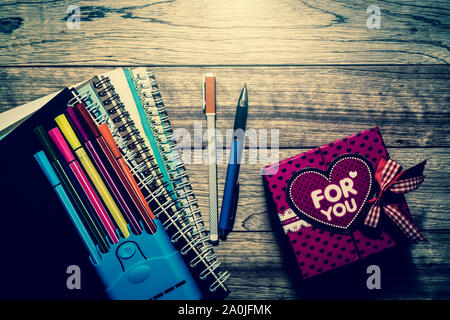Gift box, notebooks and pens on wooden plank under light in vintage style - Stock Photo