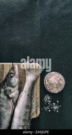 Raw fish on grill fry pan with condiments himalayan salt food photography - Stock Photo