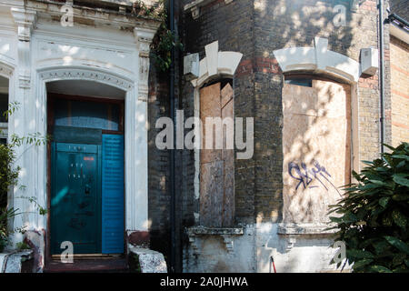 Boarded up derelict housing in Clapton, Hackney, East London, UK - Stock Photo