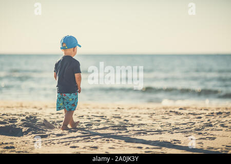 Toddler boy walking on a sunny beach. Little child walking on sand. Beautiful inspirational beach and ocean view, landscape. Stock Photo