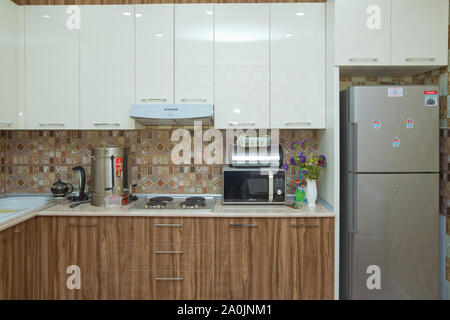Brown and white Kitchen design, refrigerator . Modern kitchen with brown kitchen cabinets, oversized kitchen . Stylish interior with dining - Stock Photo