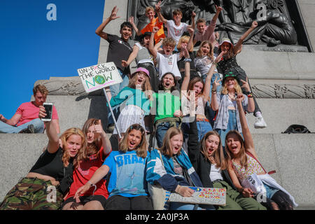 Westminster, London, UK, 20th Sep 2019. A group of school kids make it to Nelson's Column. As the afternoon progresses, protesters make their way down Whitehall, and towards Trafalgar Square. Tens of thousands of children, young people and adults protest for climate action and against the causes of climate change in the British capital. Many similar protests take place in cities around the world in a day of global climate action. - Stock Photo