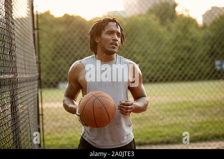 African-American man playing basketball outdoors - Stock Photo
