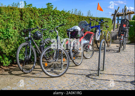 Bansin, Germany - September 13, 2019: Parked bicycles in the coastal town of Bansin on the island of Usedom, Germany. A children's bicycle was piggyba - Stock Photo