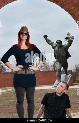 Red-haired woman wearing a soldier's hat and a tatooed man in his 20's visits Socialist dictatorial figures and memorials at Memento Statue Park,  Bud - Stock Photo