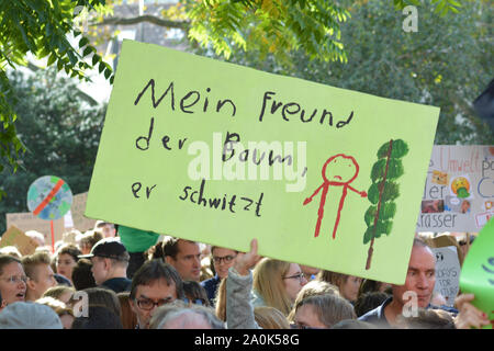 Demonstration during Global Climate Strike with cardboard banner saying 'my friend, the tree, is sweating' in German - Stock Photo