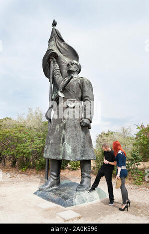 Red-haired woman wearing high heels and a tatooed man in his 20's visits Socialist dictatorial figures and memorials at Memento Statue Park,  Budapest - Stock Photo
